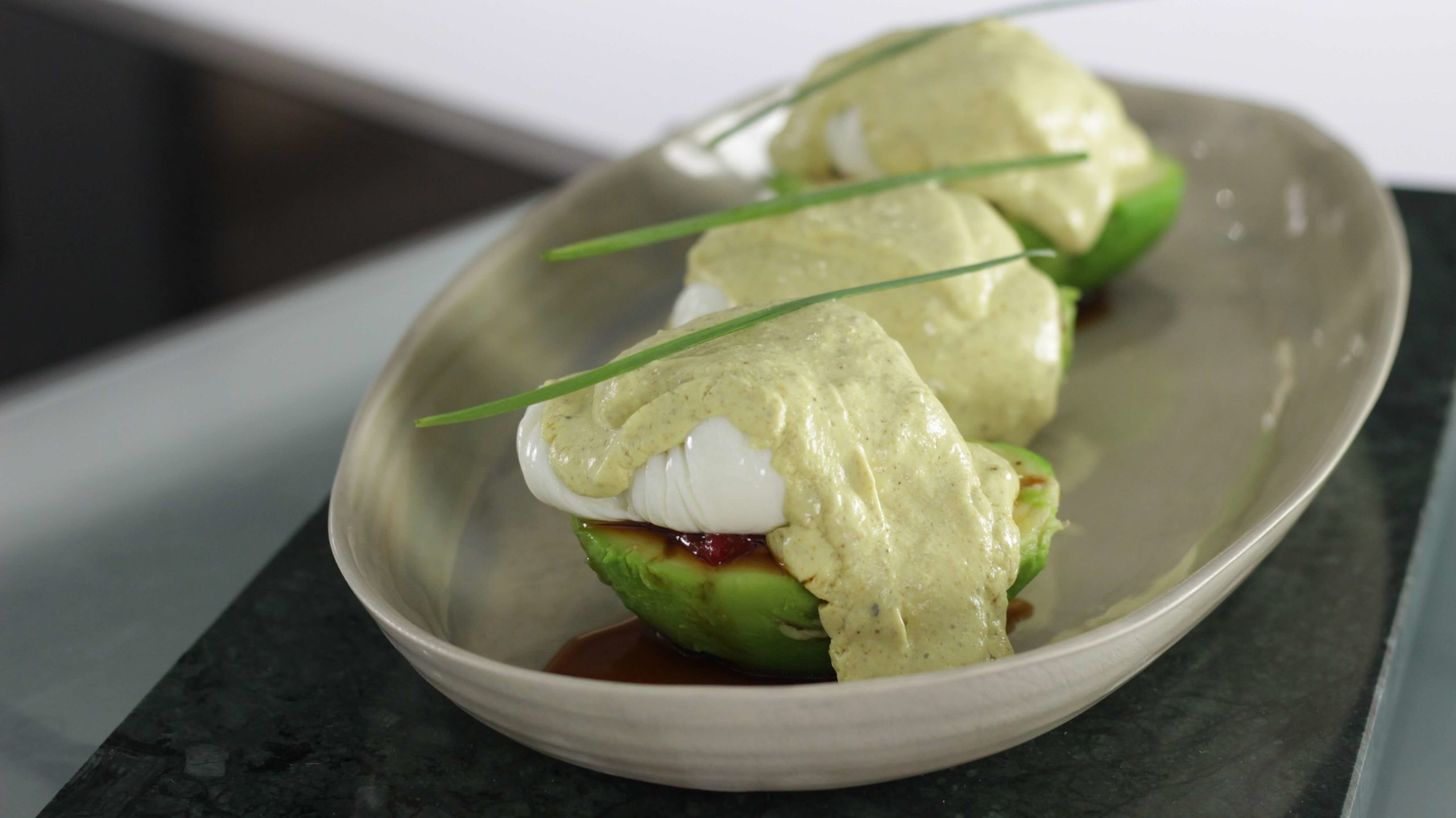 Aguacates rellenos de pimientos caramelizados con salsa de curry y huevo poché